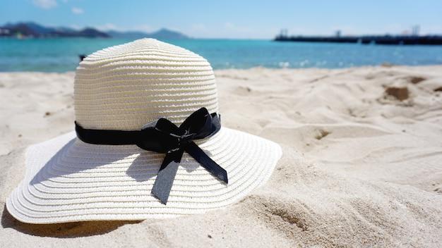 노란 모래에 모자와 함께 아름 다운 열 대 해변 푸른 바다 배경. 여행 컨셉