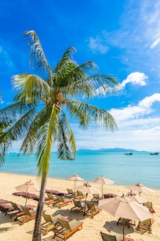 Beautiful tropical beach sea and ocean with coconut palm tree  and umbrella and chair on blue sky