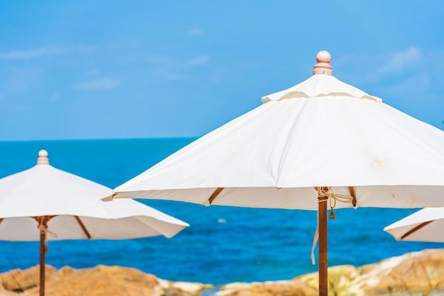 휴가 여행을위한 흰 구름과 푸른 하늘 주위에 우산과 의자가있는 아름다운 열대 해변 바다