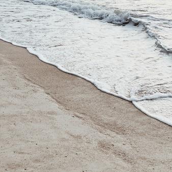 Красивый тропический пляж с белым песком и морем с белыми пенистыми волнами