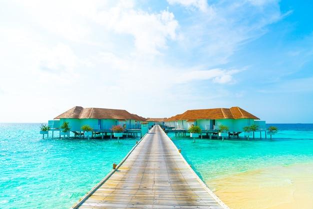 美しい熱帯モルディブのリゾートホテルとビーチと海のある島-休日の休暇のコンセプト