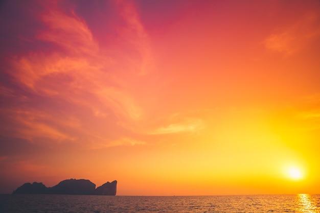 Красивый тропический закат в краби, таиланд. драматическая и живописная вечерняя сцена. океан и красочное оранжевое облачное небо на заднем плане. природный пейзаж. фон путешествия. ярко-фиолетовое тонирование