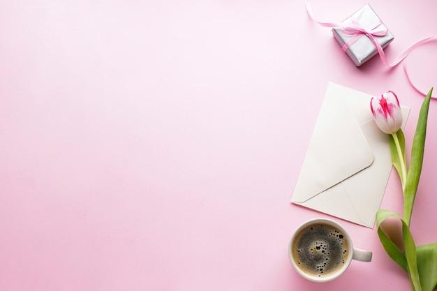 Красивый тюльпан, письмо с подарком и чашка кофе на розовом фоне, плоская планировка.