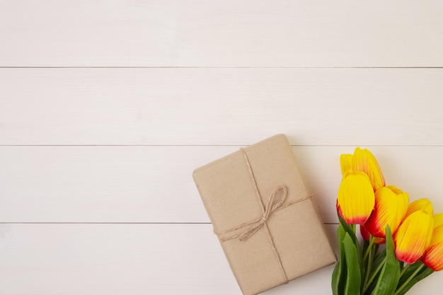 Beautiful tulip flower and gift box on wooden background with romantic, presents for mother day with pastel tone