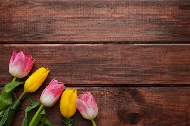 暗い木製の背景に美しいチューリップの花
