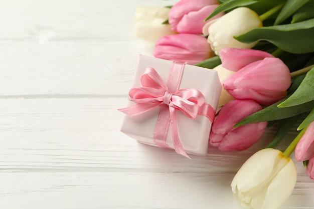 Красивые тюльпаны и подарочная коробка на белом деревянном фоне