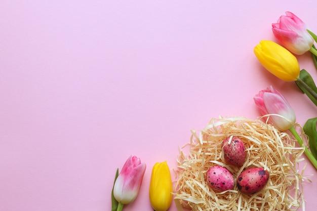 色付きのウズラの卵と美しいチューリップと巣