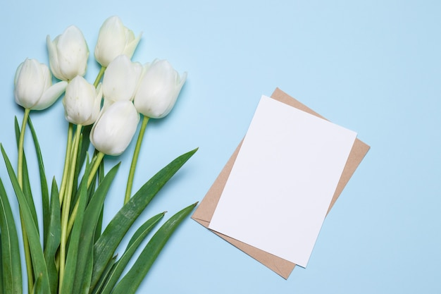 Beautiful tulips bouquet, card for text on wooden background top view.