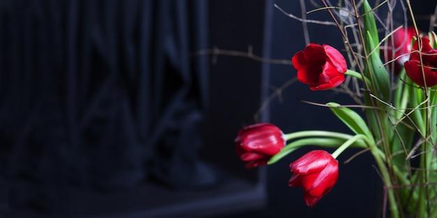 Красивый цветок тюльпанов красный цвет в стеклянной вазе на черном фоне. день святого валентина или день матери поздравительных открыток. скопируйте место для текста. баннер