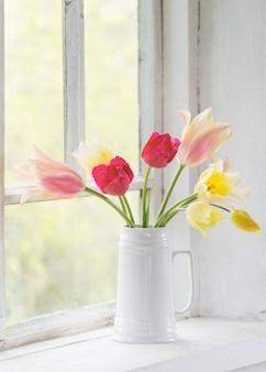 白い窓辺に花瓶の美しいチューリップ