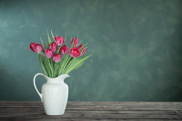 Красивые тюльпаны в белом кувшине на темноте