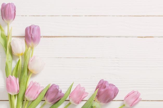 白い木製の背景に美しいチューリップ