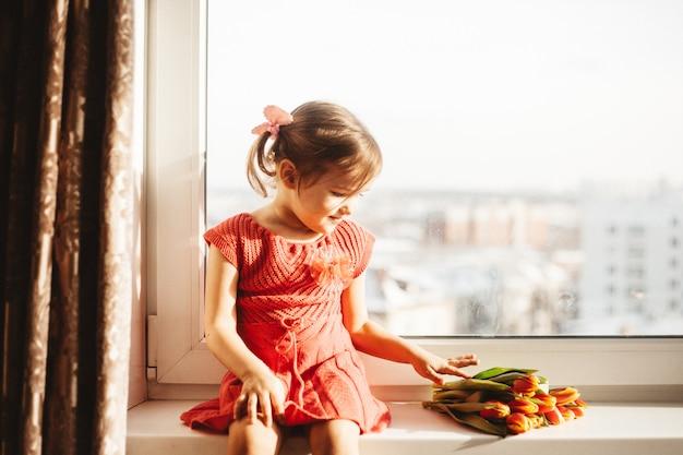 美しいチューリップ、春の花。ウィンドウの上に花瓶のチューリップ
