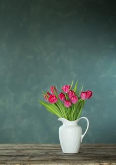 Beautiful tulips in white jug on dark background