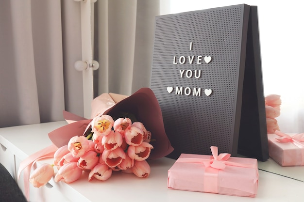 文字盤の看板にilovemomの文字が入った美しいチューリップ。ピンクの背景、フレーム、ボーダー。母の日、結婚式、または幸せなイベントのコンセプトのためのチューリップが付いた素敵なグリーティングカード。