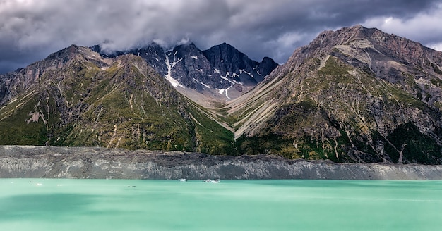 Beautiful turqouise tasman glacier lake and rocky mountains in the clouds, mount cook national park, south island, new zealand