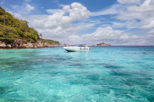 Красивое бирюзовое море и парусная яхта с горами и голубым небом с облаками.