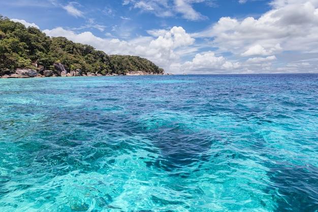 Красивое бирюзовое море с горами и голубое небо с облаками пейзаж