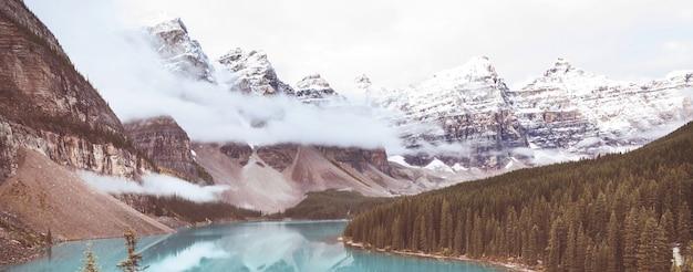 Красивые бирюзовые воды озера морейн с заснеженными вершинами над ним в национальном парке банф в канаде.