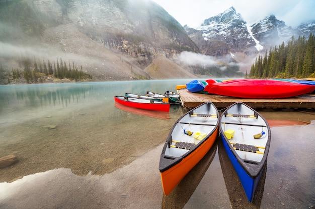 カナダのバンフ国立公園の上に雪に覆われた山頂があるモレーン湖の美しいターコイズブルーの海