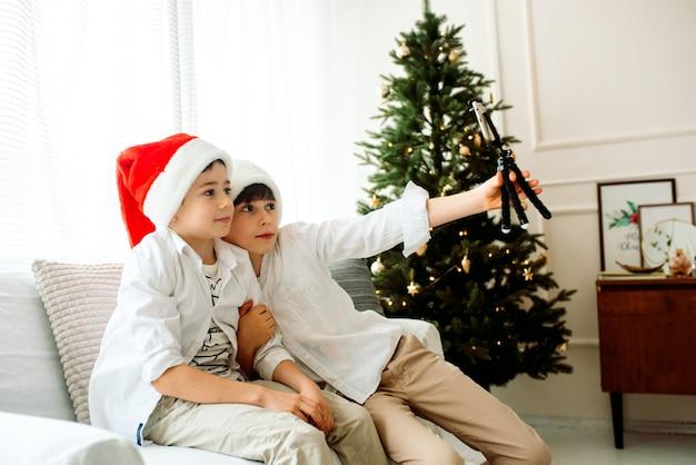 携帯電話で自分撮りをしている自宅の美しい二人の兄弟。クリスマスツリーのそばに座っている幸せな子供たち。