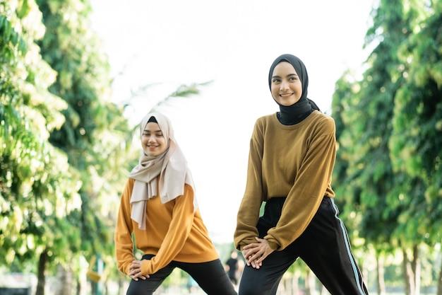 スカーフの美しい2人のイスラム教徒の女の子は、公園でのアウトドアスポーツの前に突進運動をします