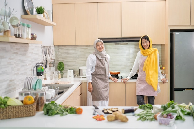 Beautiful two muslim woman enjoy cooking dinner together