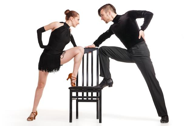 흰색 배경 위에 의자를 가지고 춤추는 아름다운 두 명의 전문 예술가