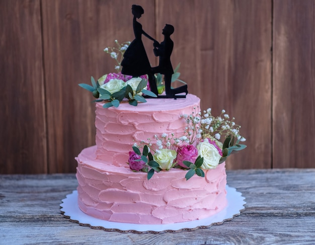 Beautiful two-tiered wedding cake with pink cheese cream, decorated with live roses and a figure of a couple in love, on a wooden table