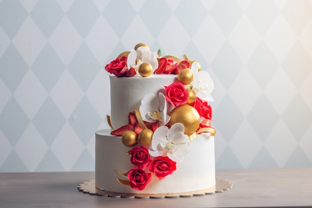Beautiful two-tiered white wedding cake decorated with red roses