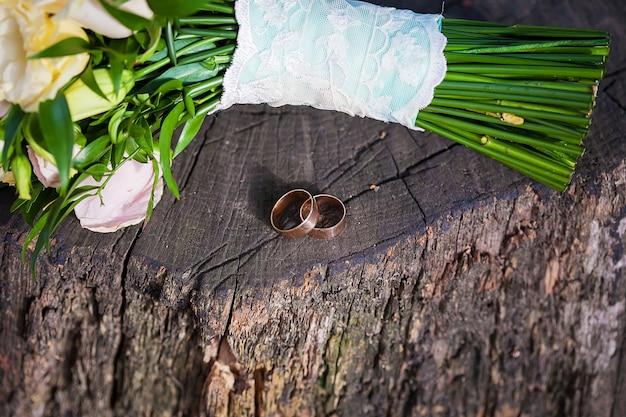 Красивые два обручальных кольца на деревянном пне и кусок букета