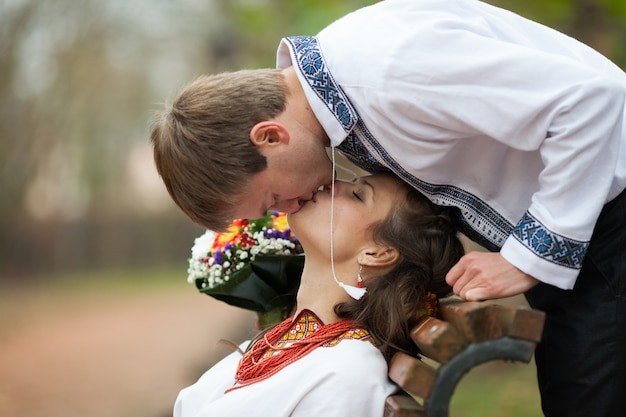Beautiful ukrainian bride and groom in native embroidery suits kissing on a bench on the background of trees in a park