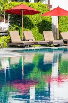 休日休暇旅行のためのホテルリゾートの屋外スイミングプールの周りの美しい傘と椅子