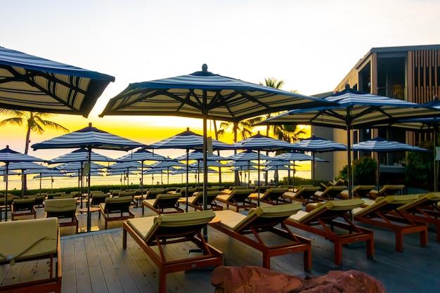 Красивый зонт и стул вокруг открытого бассейна в курортном отеле с закатным небом для праздничных каникул, путешествий