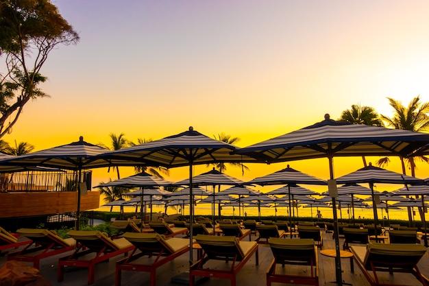 休日の休暇旅行のための夕焼け空とホテルリゾートの屋外スイミングプールの周りの美しい傘と椅子