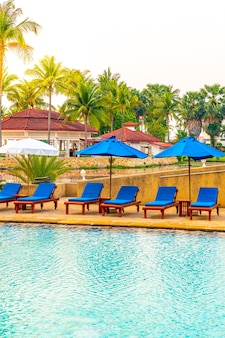 Красивый зонт и кресло вокруг бассейна в отеле и на курорте - отпуск и праздничный концерт