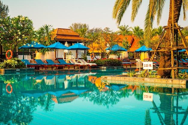 호텔과 리조트의 수영장 주변에 있는 아름다운 우산과 의자 - 휴가 및 휴가 콘서트
