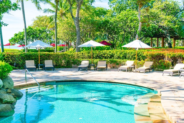 ホテルとリゾートのプールの周りの美しい傘と椅子-休暇のコンセプト