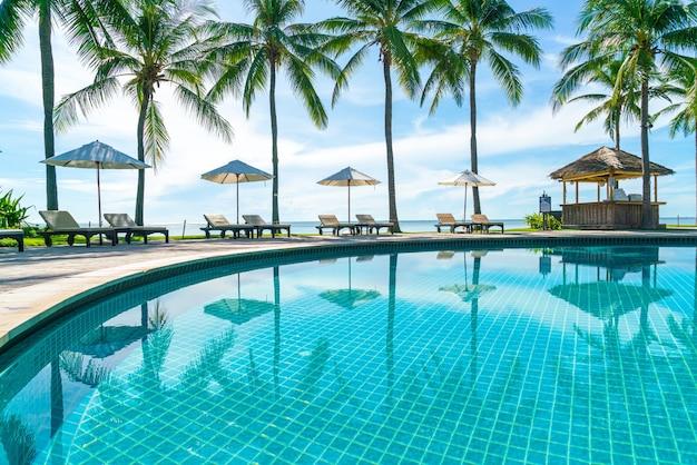 ホテルやリゾートのプールの周りの美しい傘と椅子