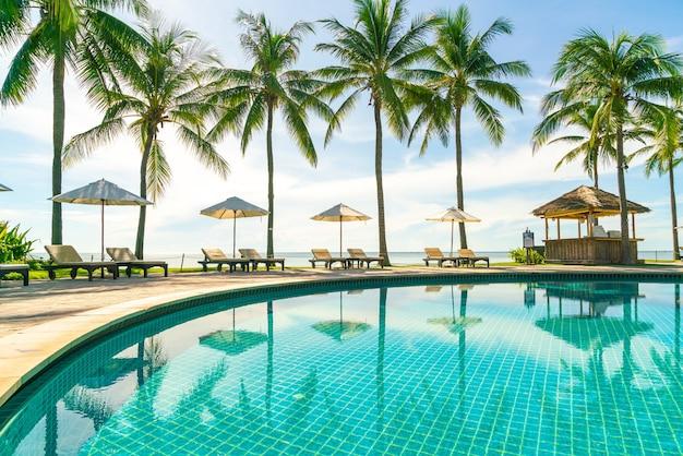 Красивый зонт и кресло вокруг бассейна в отеле и на курорте