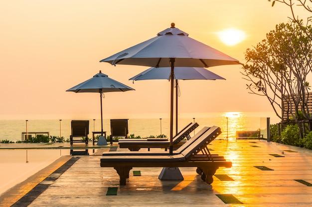 ホテルとリゾートのプール周辺の美しい傘と椅子