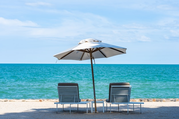 Beautiful umbrella and chair around beach sea ocean with blue sky for travel