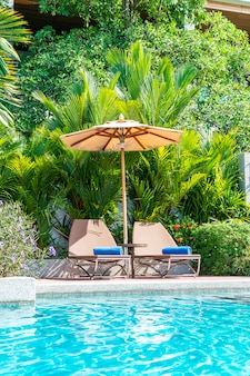 Beautiful umbrella and chair around swimming pool in hotel and resort - vacation concept