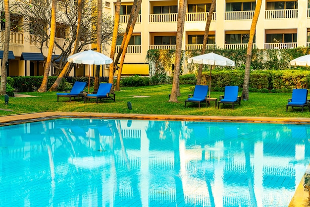 Beautiful umbrella and chair around swimming pool in hotel and resort - vacation and holiday concert