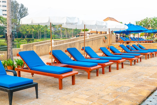 Beautiful umbrella and chair around swimming pool in hotel and resort