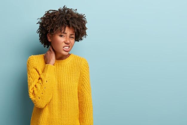 Bella donna infelice con un afro in posa in un maglione rosa