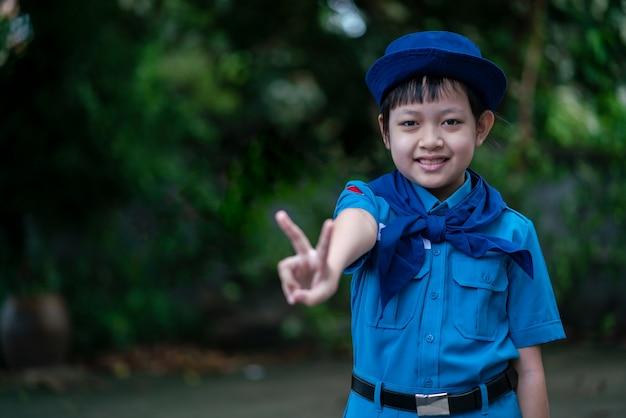 Красивая скаутская девушка в униформе, стоящая и показывающая пальцами, подписывает со счастливой улыбкой