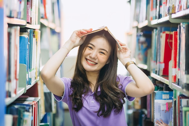 Beautiful university girl reading a book in library. concept for learning and education.