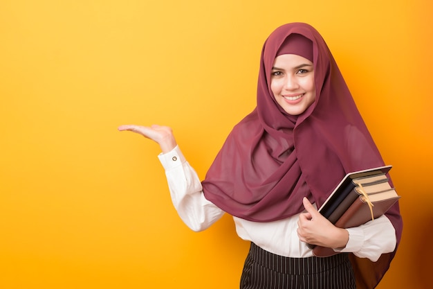 Beautiful university student with hijab portrait on yellow background