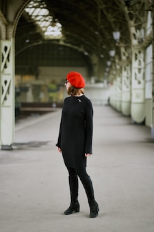 Beautiful unrecognizable woman is waiting for train on railway station.